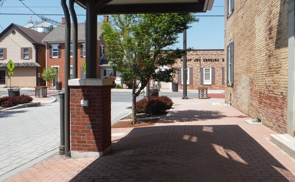 Looking north, covered walkway with pavers and landscaping