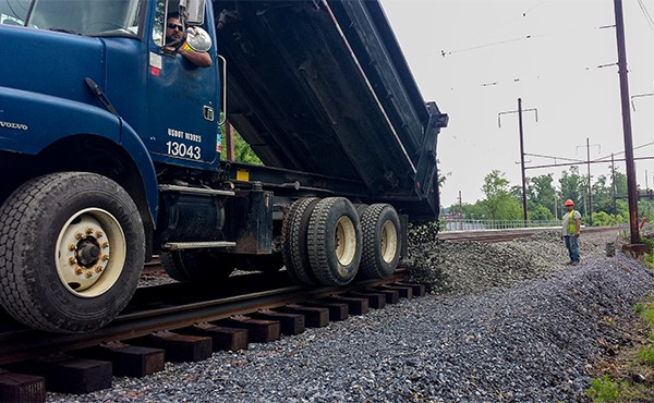 Hi-rail dump truck distributing ballast (May 2019)