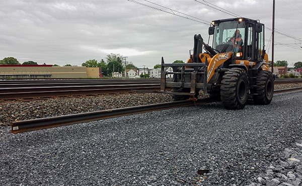 Front end loader moving welded rail string down the line (May 2019)