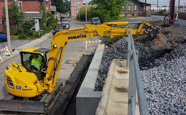 Placing stone on slope above retaining wall (May 2019)