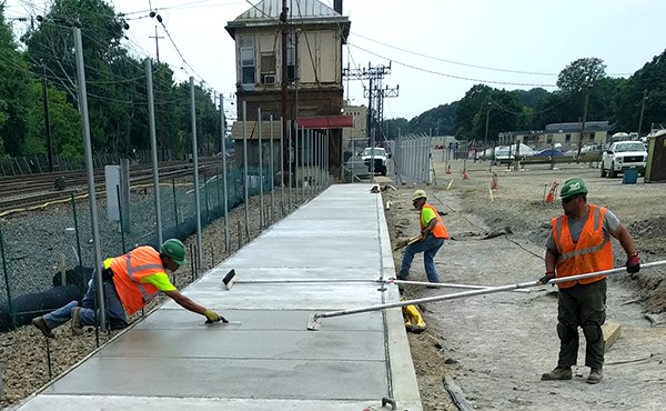 Troweling new sidewalk in northwest parking lot (July 2017)