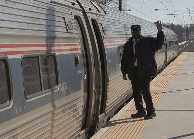 Photo of Amtrak conductor waving from platform as train prepares to depart a station.