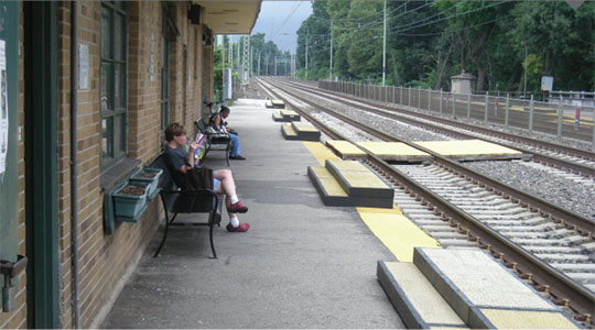 Photo of the Ardmore Station eastbound platform, looking west. Two waiting passengers are visible along with low-level platforms and the trackside face of the Ardmore Station building.