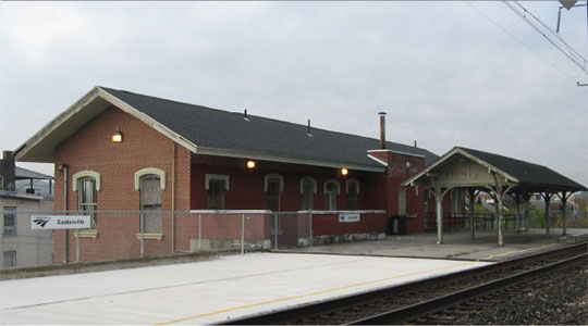 Photo of the historic Coatesville Station building and passenger shelter viewed from trackside.