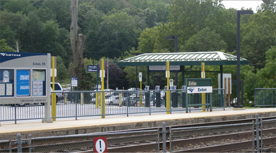 Photo of low-level platform, station sign, and canopy at Exton Station as viewed from trackside.