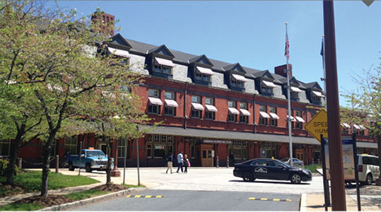Photo of the historic Harrisburg Transportation Center building from the front. Pedestrians, a taxi, and vehicles are visible in the front parking area.