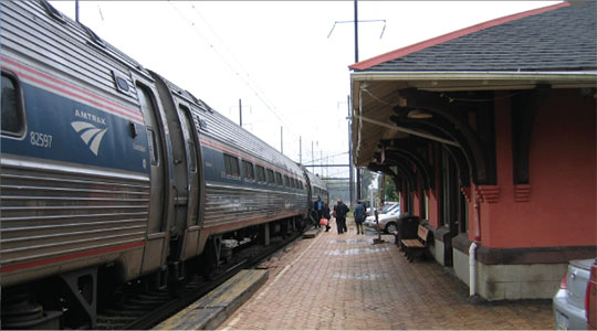 Photo of an Amtrak train in front of the historic Parkesburg station building, looking east along the low-level platforms.