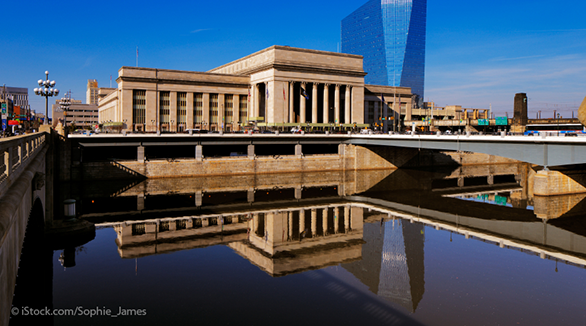 Professional photograph of Philadelphia's 30th Street Station and its reflection in the Schuylkill River. Photo credit is ©iStock.com/Sophie_James.
